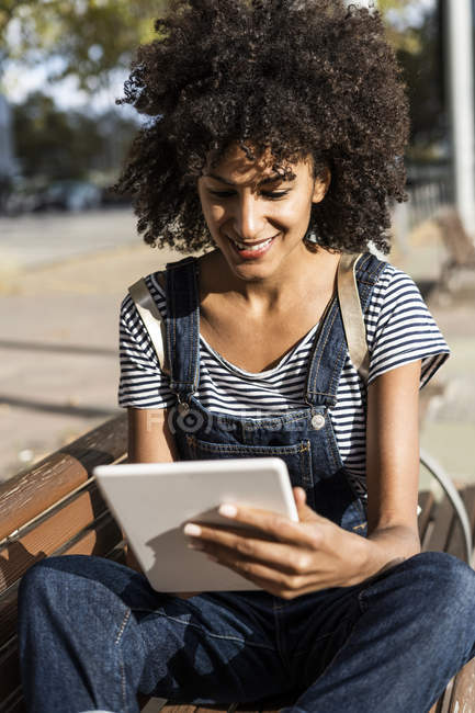 Mid adult woman with curly hair, sitting on a bench, using digital tablet — Stock Photo