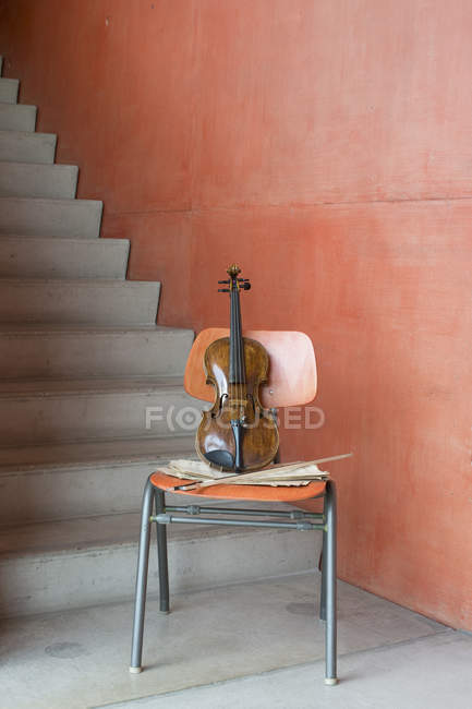 Violin, bow and sheet music on wooden chair at staircase — Stock Photo