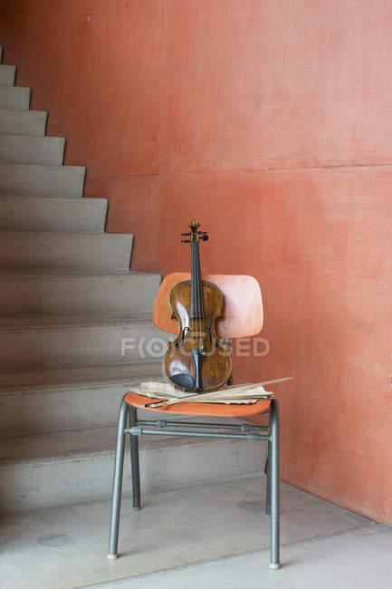 Скрипка, лук і листкова музика на дерев'яному стільці на сходових сходах — стокове фото