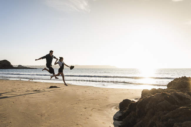 Francia, Bretagna, felice giovane coppia che salta sulla spiaggia al tramonto — Foto stock