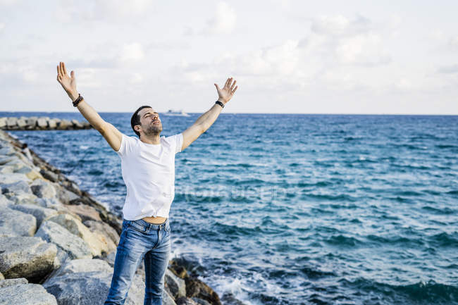 Man with raised arms and eyes closed standing in front of the sea — Stock Photo