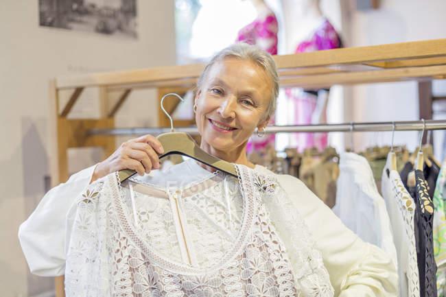Портрет улыбающейся пожилой женщины, покупающей одежду в бутике — стоковое фото