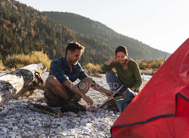 Couples mûrs campant au bord de la rivière avec le bois pour un feu de camp — Photo de stock