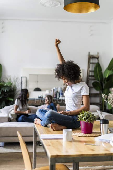 Femme encourageante utilisant tablette sur la table à la maison avec des amis en arrière-plan — Photo de stock