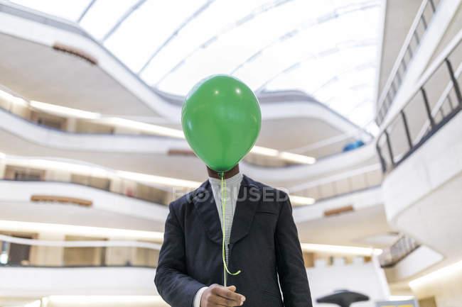 Maduro empresário escondendo rosto atrás verde balão — Fotografia de Stock