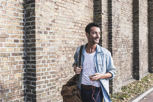 Mature man commuting in the city, carrying bag and smartphone — Stock Photo