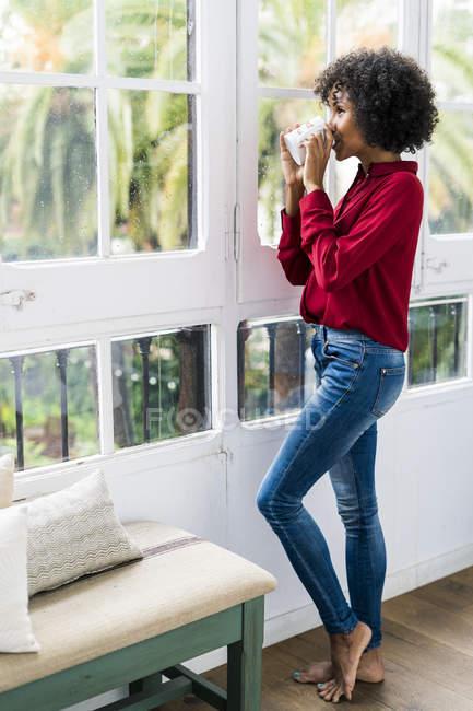 Femme regardant par la fenêtre à la maison boire une tasse de café — Photo de stock