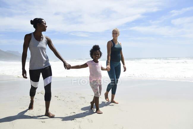 Счастливая мать с дочкой и другом гуляют по пляжу — стоковое фото