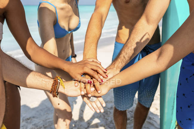 Group of friends on the beach stacking hands — Stock Photo