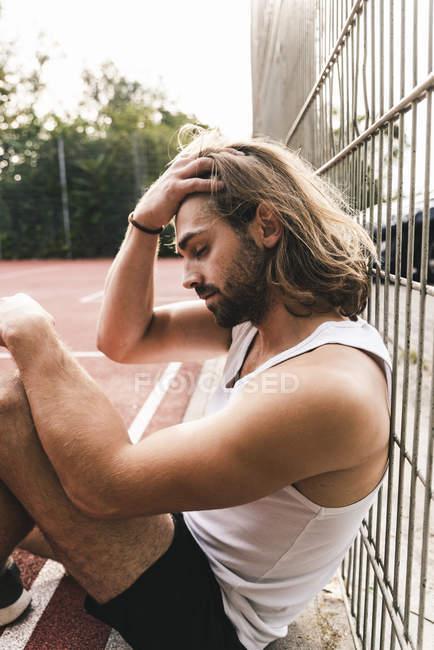 Homem novo que senta-se na terra do basquetebol, tired e disappointed — Fotografia de Stock