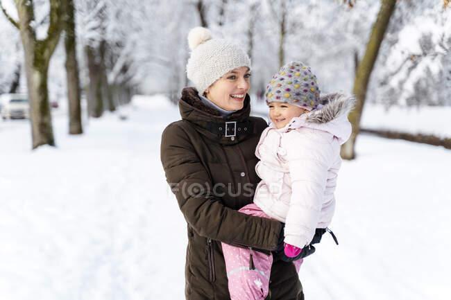Щасливі матері, несучи дочка в зимовий пейзаж — стокове фото