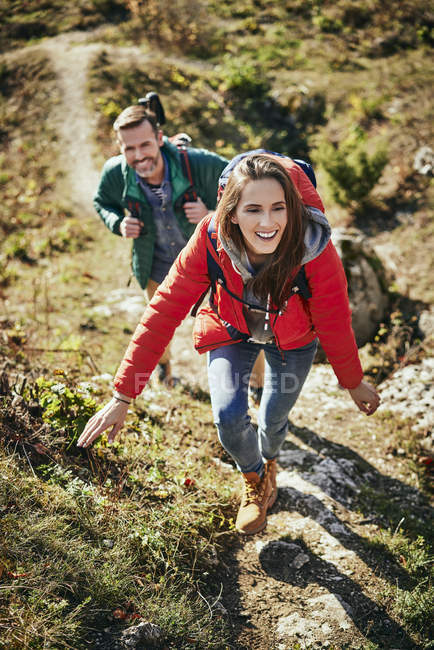 Happy couple on a hiking trip in the mountains walking up trail — Stock Photo