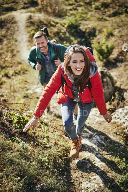 Joyeux couple en randonnée dans les montagnes en remontant le sentier — Photo de stock