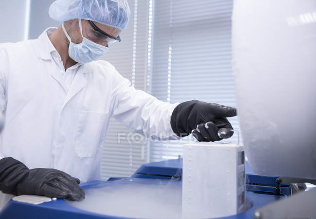 Scientist in lab storing biological material in cryo store — Stock Photo