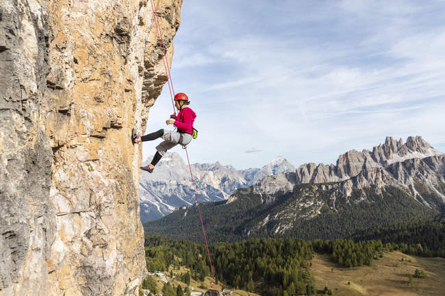 Italy, Cortina d'Ampezzo, woman abseiling in the Dolomites mountains — Stock Photo