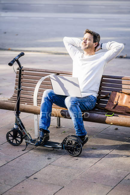 Homme d'affaires décontracté avec trottinette, assis sur un banc, travaillant détendu dans la ville — Photo de stock