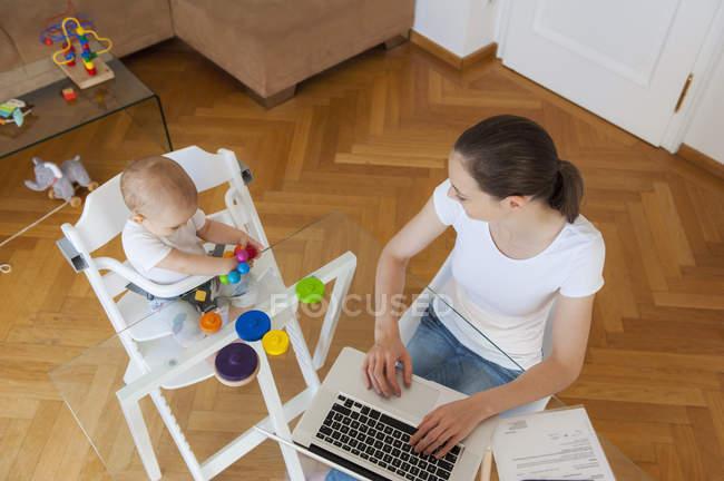 Зверху мама користується ноутбуком і маленькою донькою, яка бавиться за столом удома. — стокове фото