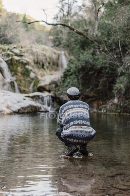 Joven parado sobre una piedra en el agua cerca de Cova Simanya, Barcelona, España . - foto de stock
