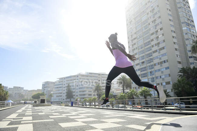 Sportive woman jumping outdoors — Stock Photo