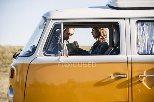 Couple on a road trip in their camper, looking at map — Stock Photo