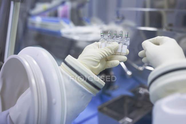 Scientifique tenant des flacons dans un laboratoire d'isolation — Photo de stock