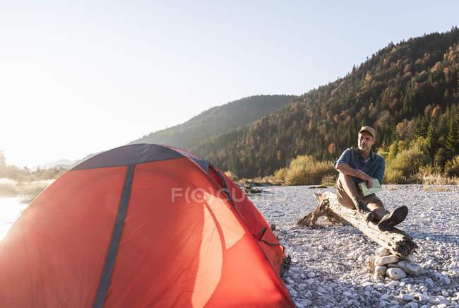 Maturo uomo campeggio a riva del fiume, seduto sul tronco d'albero con mappa — Foto stock