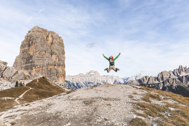 Italy, Cortina d 'Ampezzo, happy hiker jumping at the top of the mountain in the Dolomites mountains — стоковое фото