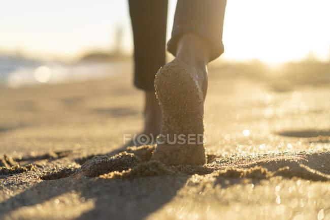 Los pies gordos de una mujer, caminando en la playa - foto de stock
