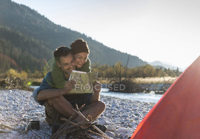 Mature couple camping at riverside, looking on map — Stock Photo
