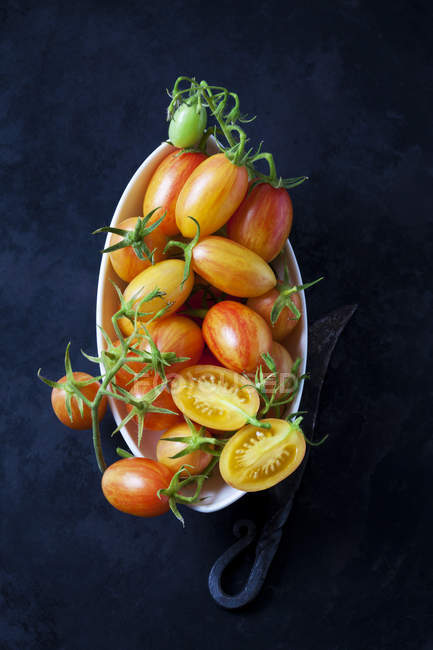 Bowl of whole and sliced cocktail tomatoes 'Artisan Blush Tiger' — Photo de stock