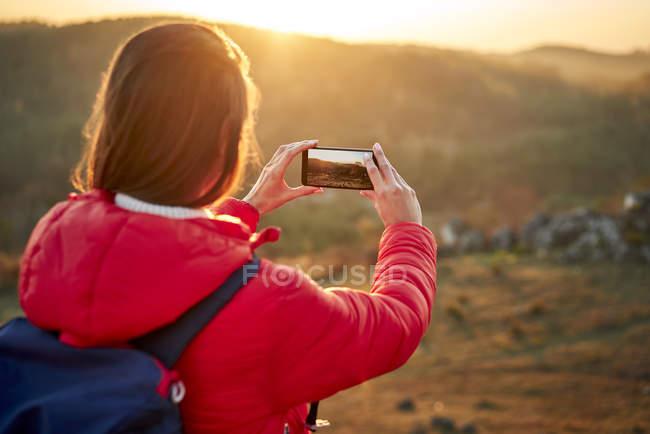 Mujer en un viaje de senderismo tomando fotos de teléfonos inteligentes al atardecer - foto de stock
