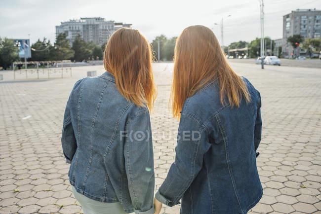 Vue arrière des sœurs rousses debout en ville — Photo de stock