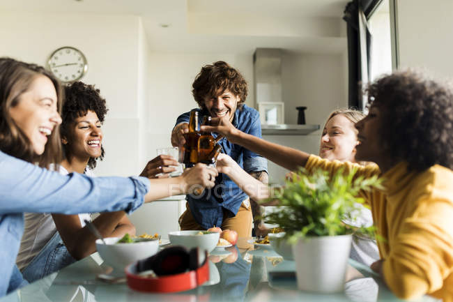 Cheerful friends clinking beer bottles at dining table — Stock Photo