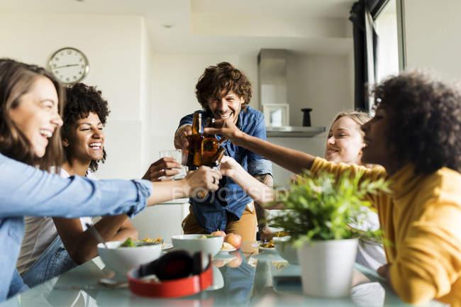 Amigos alegres que cuida botellas de cerveza en la mesa de comedor. - foto de stock