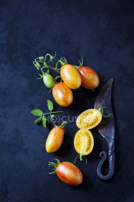 Whole and sliced cocktail tomatoes 'Artisan Blush Tiger' and an old knife  on dark ground — Stock Photo