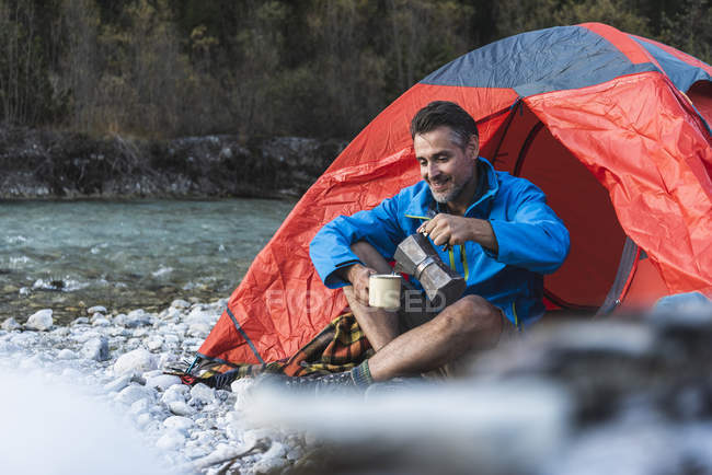 Mature man camping at riverside, espresso maker and cup — Stock Photo