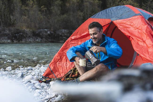 Camping d'homme mûr au bord de la rivière, fabricant d'espresso et tasse — Photo de stock