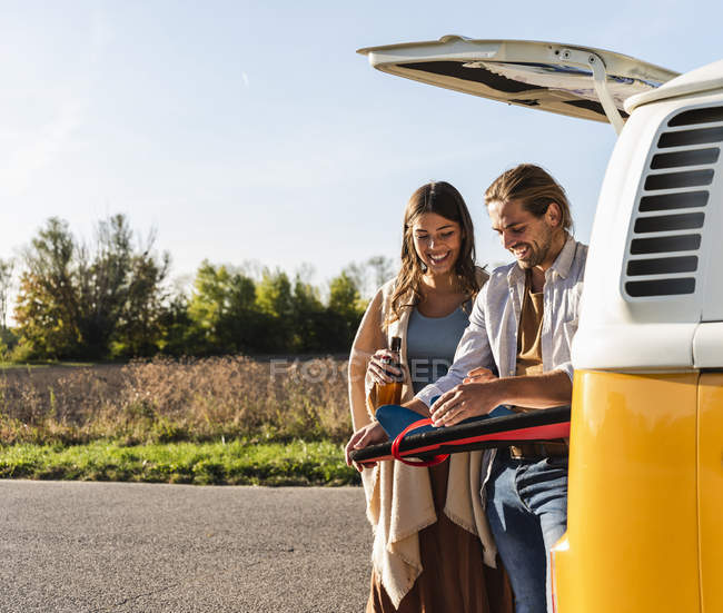 Couple on a road trip fixing surfboard at their camper — Stock Photo
