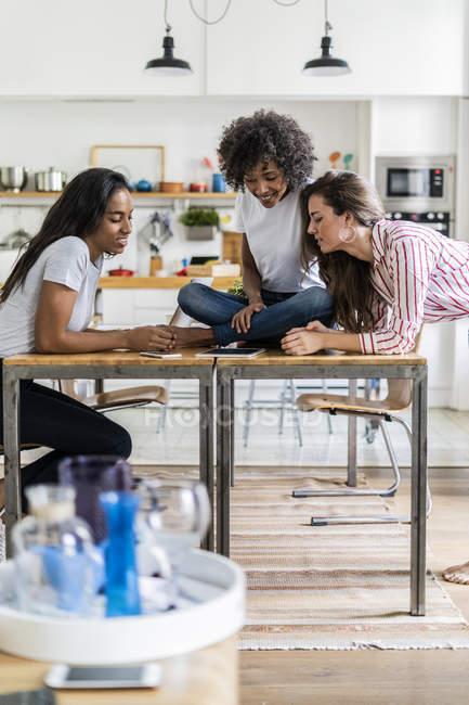 Trois femmes souriantes regardant la tablette sur la table à la maison — Photo de stock