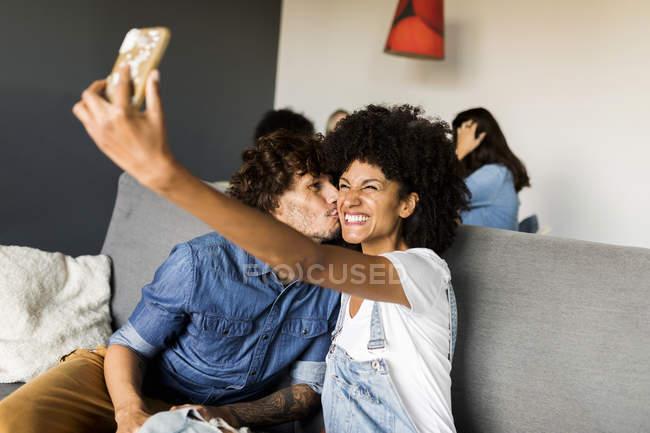 Joyeux couple assis sur un canapé et prenant une selfie — Photo de stock