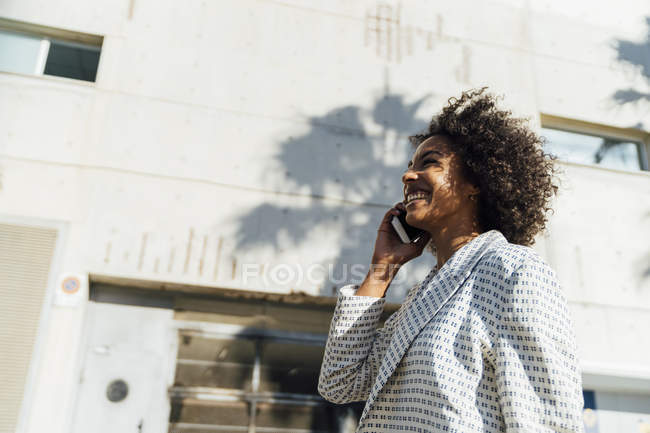 Beautiful woman walking in the city, talking on the phone — Stock Photo