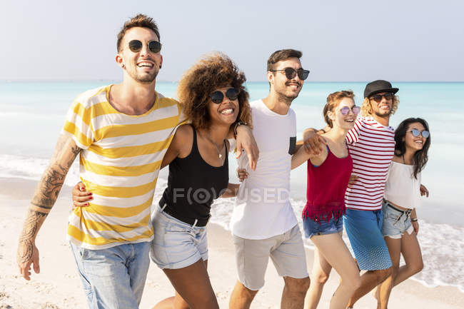 Grupo de amigos caminando por la playa - foto de stock