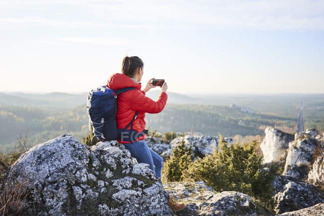 Mujer en un viaje de senderismo por las montañas tomando fotos de teléfonos inteligentes - foto de stock