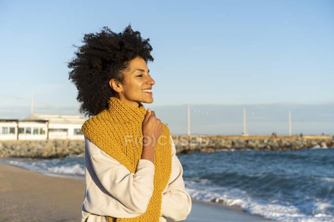 Ritratto di donna felice in spiaggia, con una sciarpa gialla — Foto stock