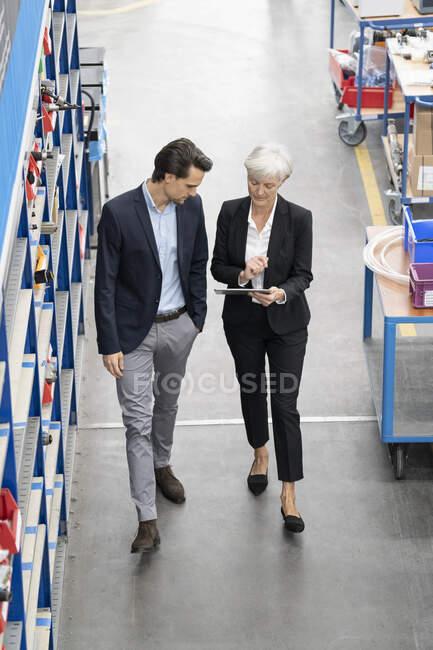 Бизнесмен и пожилая бизнесвумен с табличкой, гуляющей по фабрике — стоковое фото