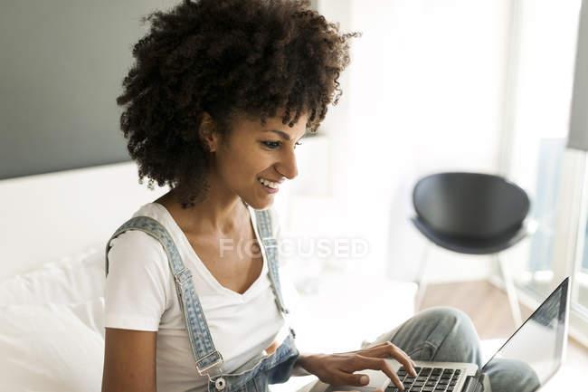 Улыбающаяся женщина сидит на кровати с помощью ноутбука — стоковое фото