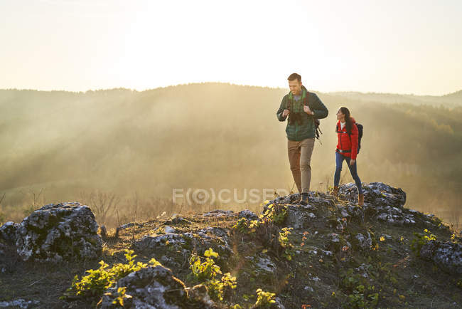Couple on a hiking trip in the mountains walking on rocks — Stock Photo