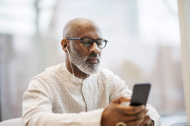 Портрет зрелого бизнесмена с помощью смартфона и наушников — стоковое фото