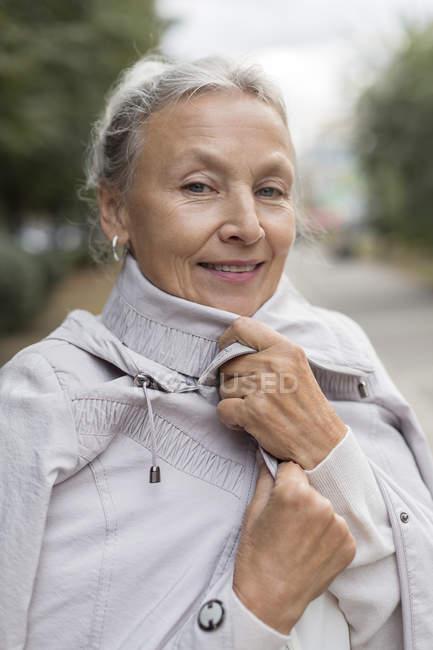 Ritratto di donna anziana sorridente che indossa un cappotto — Foto stock
