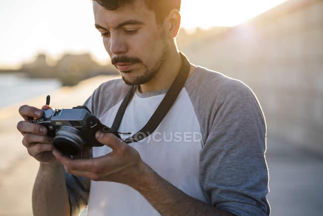 Jeune homme regardant l'appareil-photo sur la promenade de front de mer au bord de la rivière — Photo de stock